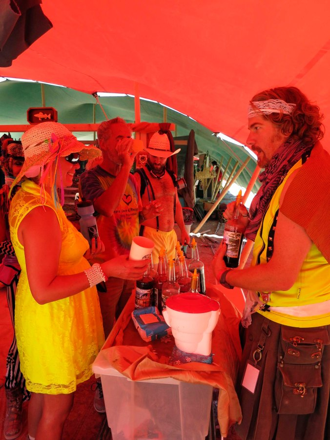 What would a souk be without exotic drinks such as a snow cone. Beth Lovering, bathed in the red glow from the tent roof, discusses flavors with the Man from Minnesota.