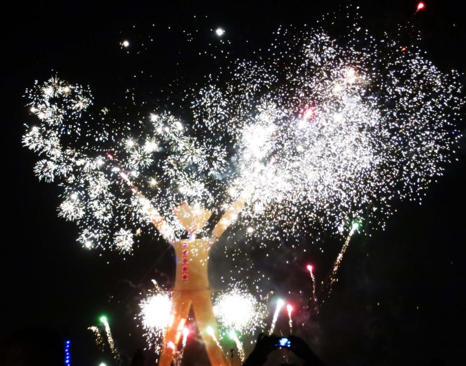 The night sky is lit up by fireworks during the burning of the Man at Burning Man 2014.