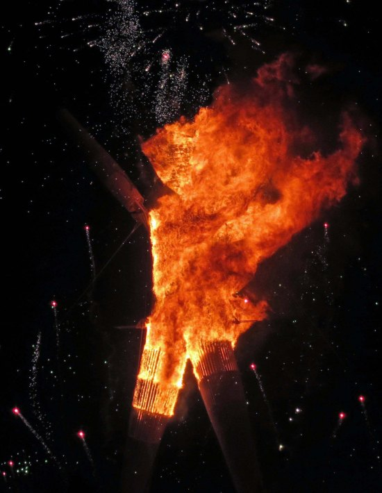 Flames shoot out as the Man burns at Burning Man 2014.