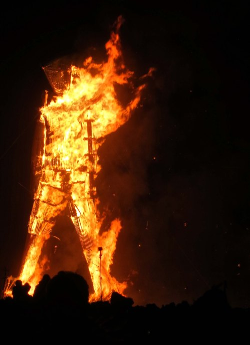 Structure of Man at Burning Man 2014 shows through the fire.