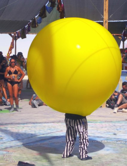 Man disappears into large yellow balloon at Burning Man 2014.