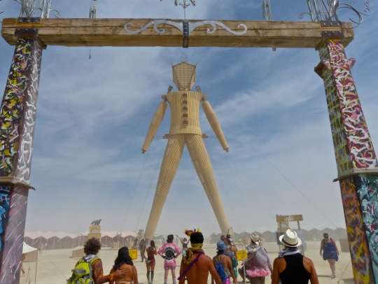 A photo of the Man at Burning Man in 2014 framed by the gateway that leads into the market place and Man.