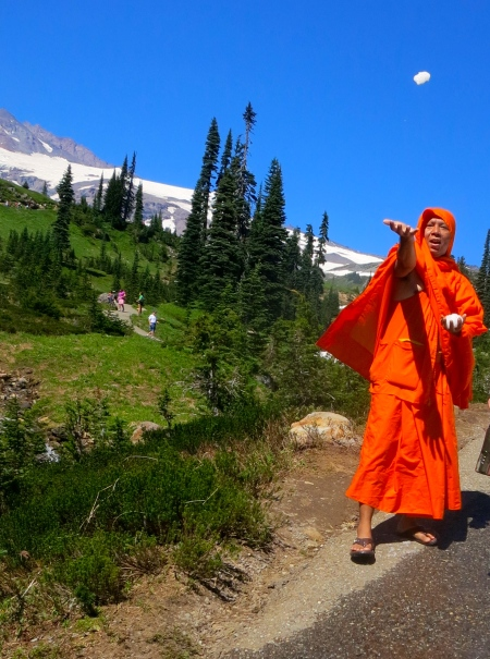 Saffron robed monk throws snowball on trail above Jackson Memorial Center at Mt. Rainier National Park. Photo by Curtis Mekemson.