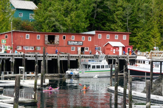 Telegraph Cove is all about water as this photo suggests. Here we see the Whale Interpretive Center, a fishing boat, and kayakers. (Photo by Peggy Mekemson.)