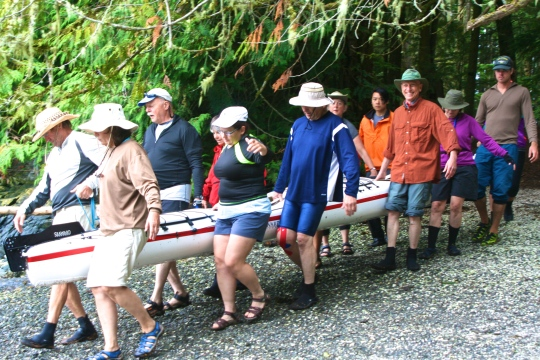 Our layover was not designed to be a kick-back and relax day. Here we are carrying our kayaks down to the water. The number of people required to move Peggy and my kayak suggests how heavy it was.  (Photo by Peggy Mekemson.)
