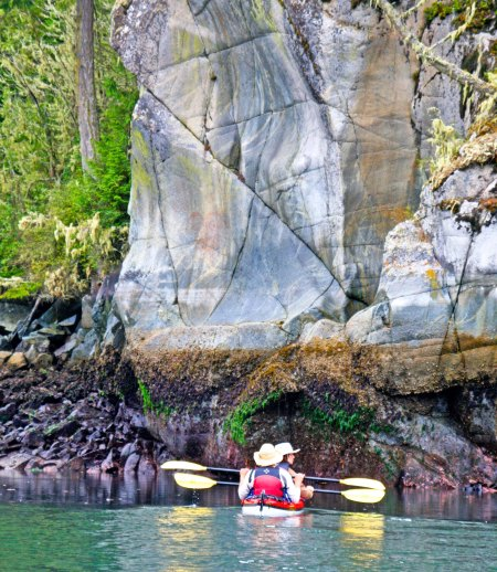 Mary and Rod, two of our kayakers from Idaho, paddle up close to get a look at the pictograph. It was above there right paddles on the shaded rock face. Can't see it? Don't feel bad; neither could I. (Photograph by Peggy Mekemson.)