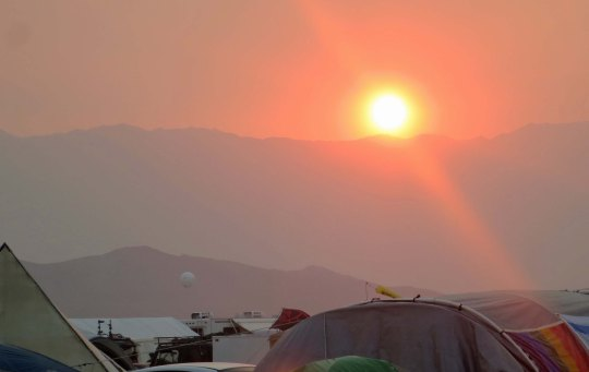 Sunset reflected through a dusty haze from our campsite at Black Rock City.