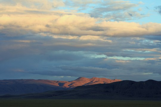 Mountains in Black Rock Desert reflect late evening sun.