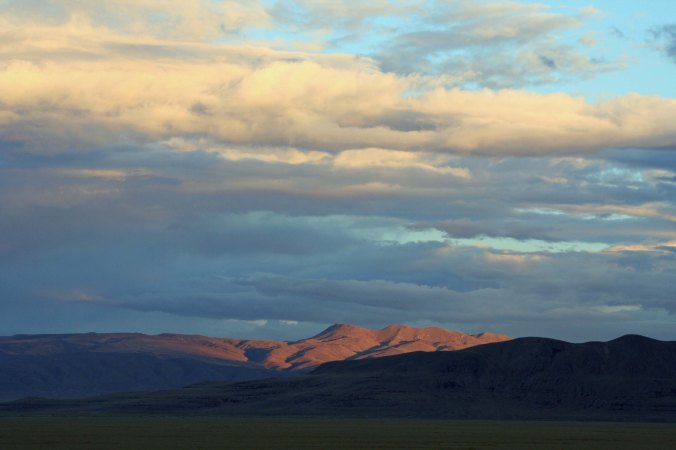 Mountains in Black Rock Desert reflect late evening sun.