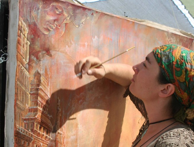 A artist works on a painting at the Center Camp Cafe, providing Burners with an opportunity to watch her work.