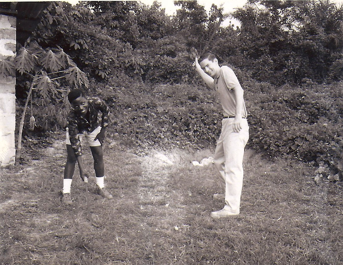 Sam and I cut back weeds with machetes in front of our house in Gbarnga, Liberia. Our outhouse is off to the left.