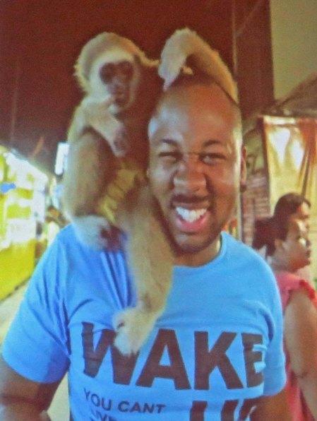 Monkey wraps itself around Eric's head.