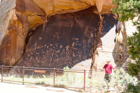 Newspaper Rock. I am standing beside the National Historic Site to provide perspective. (Photo by Peggy Mekemson.)