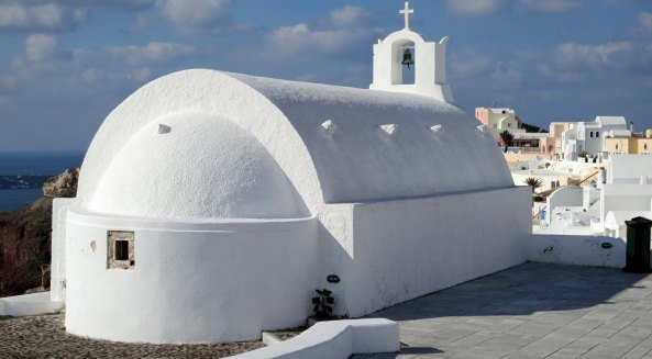 A back view of the church with Oia, Santorini stretching out in front.