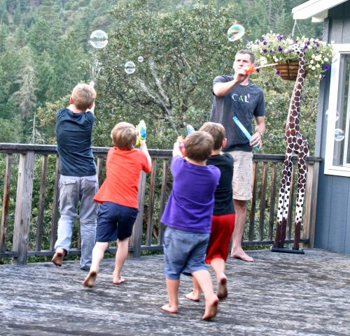 Shooting water guns accurately was practiced nightly before the big water gun fight. Four of the boys go after bubbles that Tony is creating.