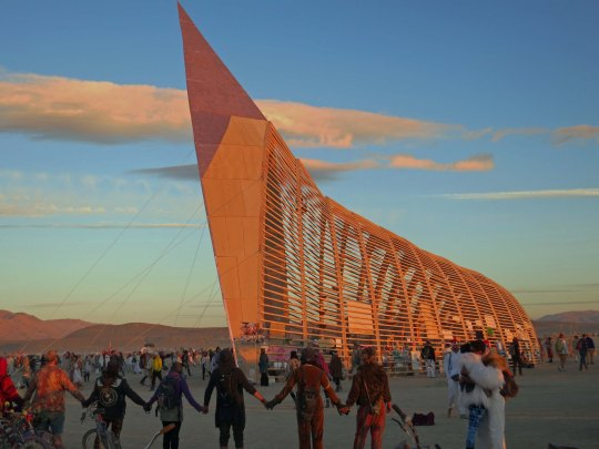 The Burning Man Temple at sunrise is guaranteed to draw a crowd. Burners had spontaneously joined hands as the sun little up the Temple.