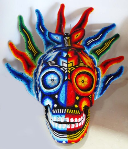 Okay, this skull is wild! The art is created by laying lines of beads into wax, a process used by the Huichol indians.