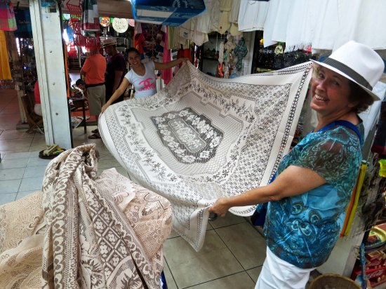 Peggy checks out a new table cloth she is buying. The day before we had checked it out and Peggy had mentioned she wanted the edges sewn. The young woman took the tablecloth home that night and did the work.