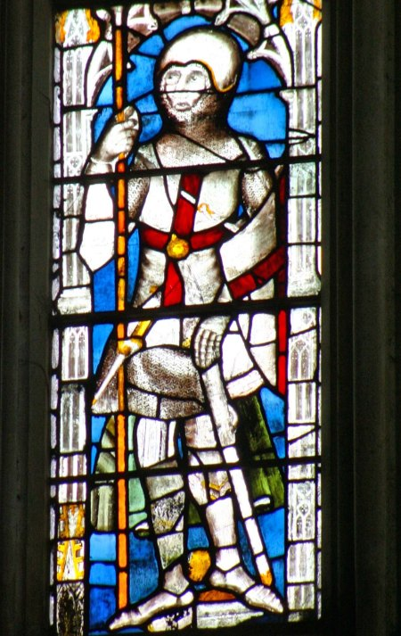 An early stained glass window featuring a knight.