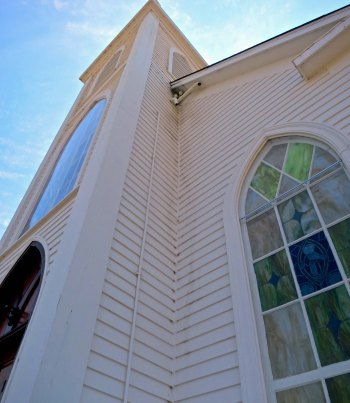 A front view of St. Teresa's Catholic Church showing a stained glass window.