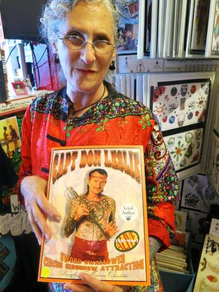 Madam Chinchilla holds the book she wrote on Captain Don.