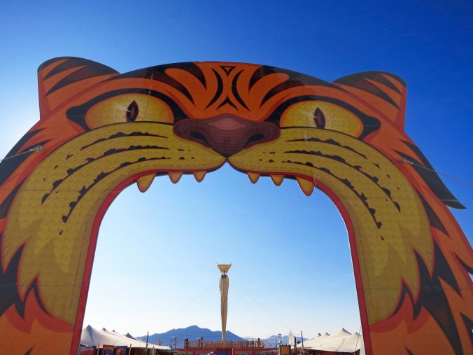 """One of four gateways to the 2015 Burning Man carnival. William Blake's poem """"TIGER, tiger, burning bright. In the forests of the night,. What immortal hand or eye. Could frame thy fearful symmetry?"""" was printed around the edge."""