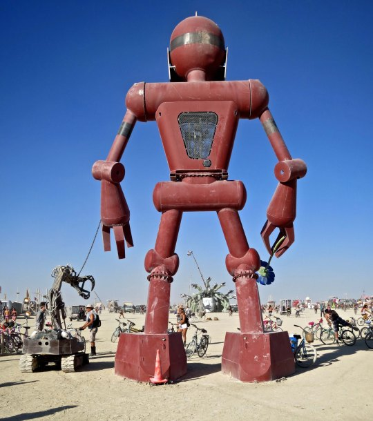 Just a 30 foot robot boy walking his robot dog at Burning Man 2015. The boy holds a flower in his right hand that he raises up to his nose and 'smell.' The endless creativity at Burning Man has brought me back to event time and again over the years.