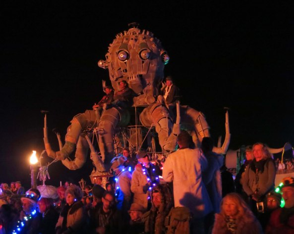 People perch on El Pulpo Mechanico at Burning Man and watch as the Man burns.