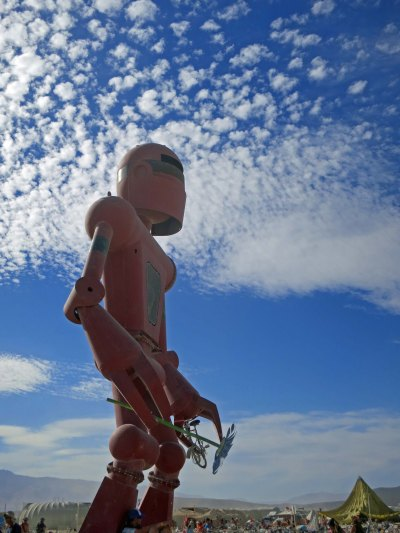 2015 Burning Man robot holds a flower in one hand and a bike in the other