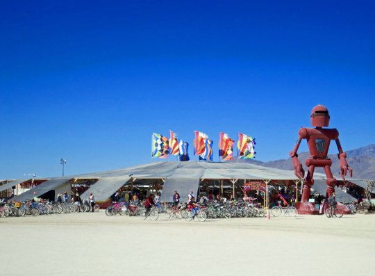 The Center Camp Cafe at Burning Man 2015. The flying flags can be seen from most places on the Playa and in Black Rock City, serving as a beacon for lost Burners. I've used them many times, especially at night when they are lit up.