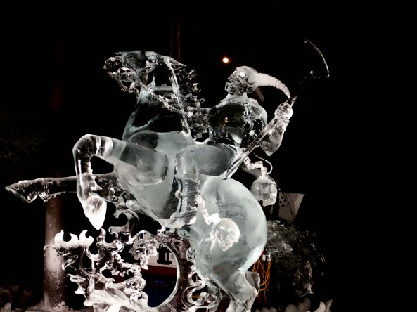 "Ice art sculpture ""Soul Collector"" lit up at night at the 2016 World Ice Art Championshipsin Fairbanks, Alaska."