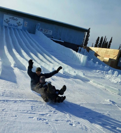 Tony and sons come barreling off one of the slick ice slides on a plastic sled peggy bought for the purpose. Yahoo!