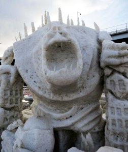 City destroying snow sculpture monster at 2016 Fur Rendezvous snow carving contest.