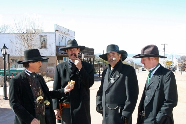 Wyatt Earp arrests Bone in Tombstone. Doc Holiday checks him for weapons.