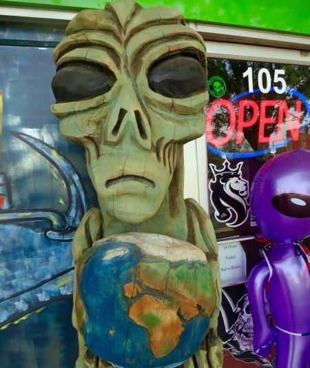A little green man contemplates what to do about earth while standing on the streets of Roswell.