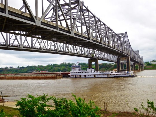 A side view of the Visalia-Natchez Bridge across the Mississippi River with a barge passing under it.