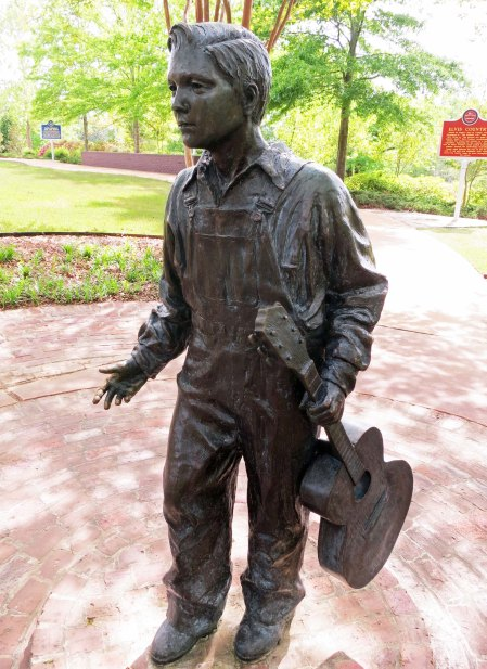 A bronze statue of the young Elvis with guitar in hand.