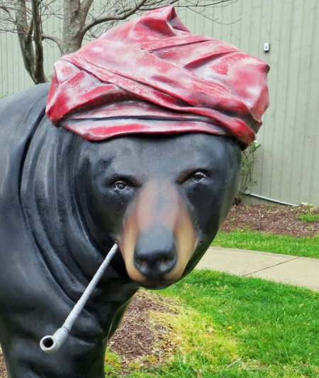 Bear sculpture in Cherokee, North Carolina smoking pie and dressed like an artist.