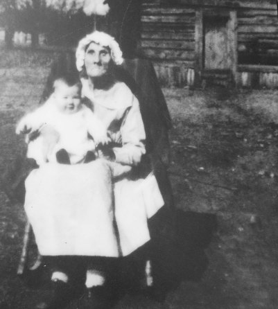 This photo of Orlena, looking 102 and holding the last child she helped be born, is next to her sister's cabin.