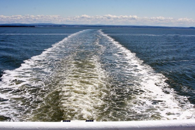 Ferry wake stretching across the broad St. Lawrence River.