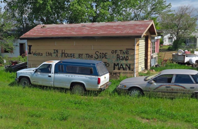 """Peggy and I came across this derelict old house with its life-affirming message along Highway 2. It's a great message for these troubled times from a poem by Sam Walter Floss: """"Let me live in a house beside the road/ Where the race of men go by/ The men who are good and the men who are bad/ As good and bad as I/ I would not sit in the scorner's seat/ Nor hurl the cynic's ban/ Let me live in a house by the side of the road/ And be a friend to man."""""""