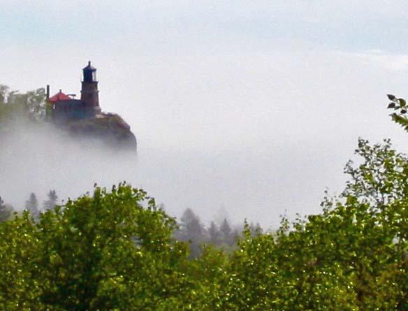 The photogenic Split Rock Light house poised on a ledge above a foggy Lake Superior.