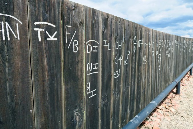 Fence showing Montana cattle brands at Culbertson, Montana museum.