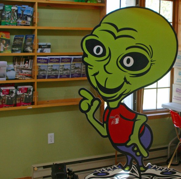 Alien points out brochures in Information Bureau in Moonbeam, Ontario Canada.