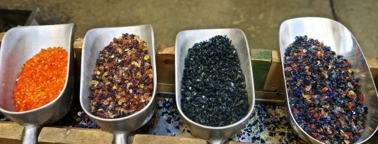 Bins that hold colored glass to add color to glass art created at the Glass Forge in Grants Pass, Oregon.