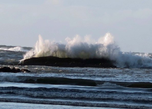 Backlit wave crashes over rock at Sunset bay near Coos Bay, Oregon.