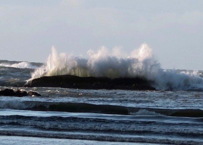 Backlit wave crashes over rock at Sunset bay near Coos Bay, Oregon.