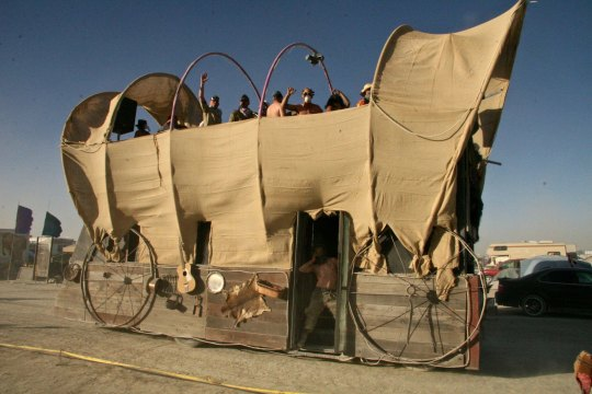 A covered wagon mutant vehicle at Burning Man.