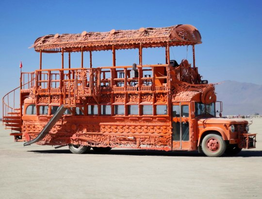 Orange mutant vehicle bus side view.