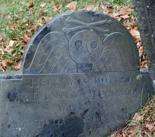 The Puritans were sensitive about elaborate headstones, wanting to keep things simple. This death's head with its crossed bones was allowed, however, and is found on many early tombstones in the New England region.